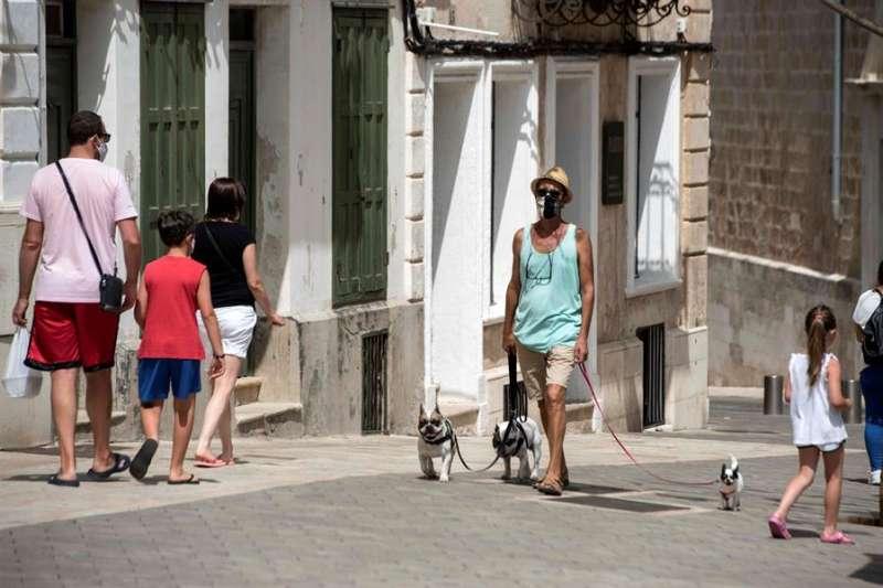 Varias personas caminan por las calles de Mahón (Menorca, España) protegidas con mascarilla. EFE/ David Arquimbau Sintes
