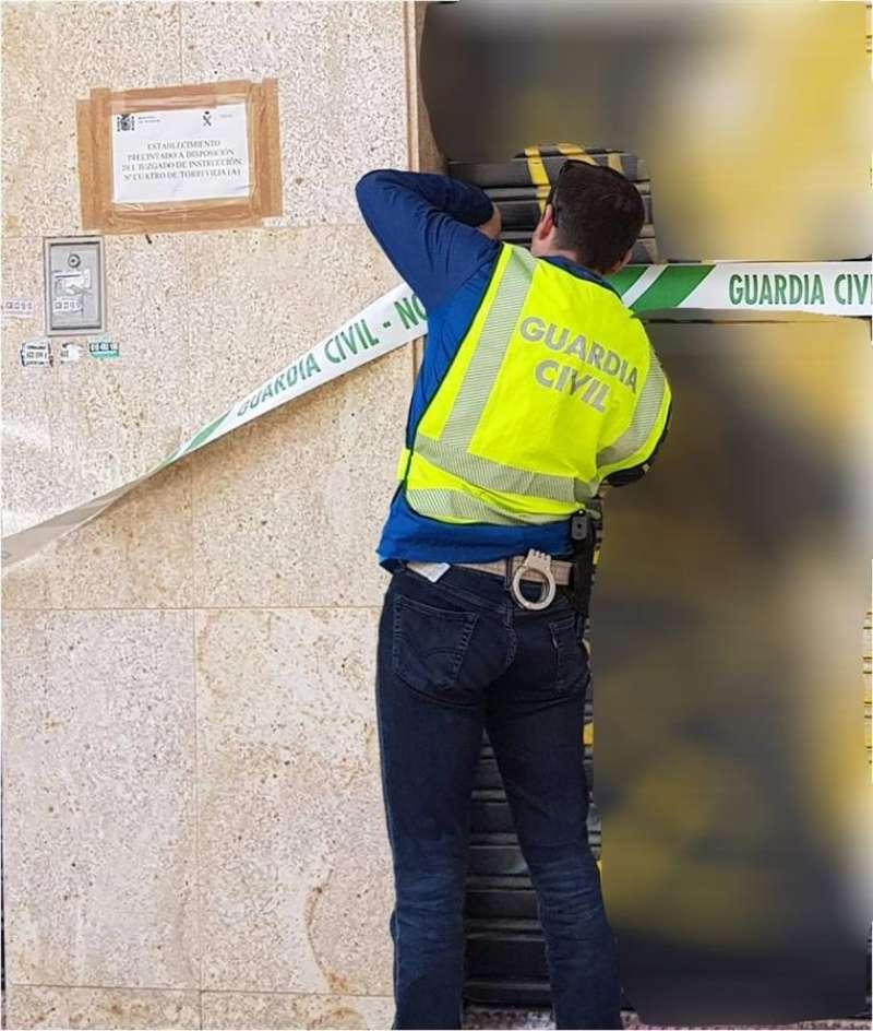 Un agente procede al precinto del local, en una imagen distribuida por la Guardia Civil