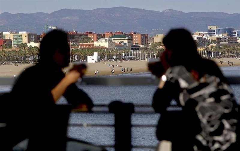 Imagen de archivo de una pareja en una terraza de la dársena del Puerto de València, con la playa de la Malvarrosa al fondo. EFE
