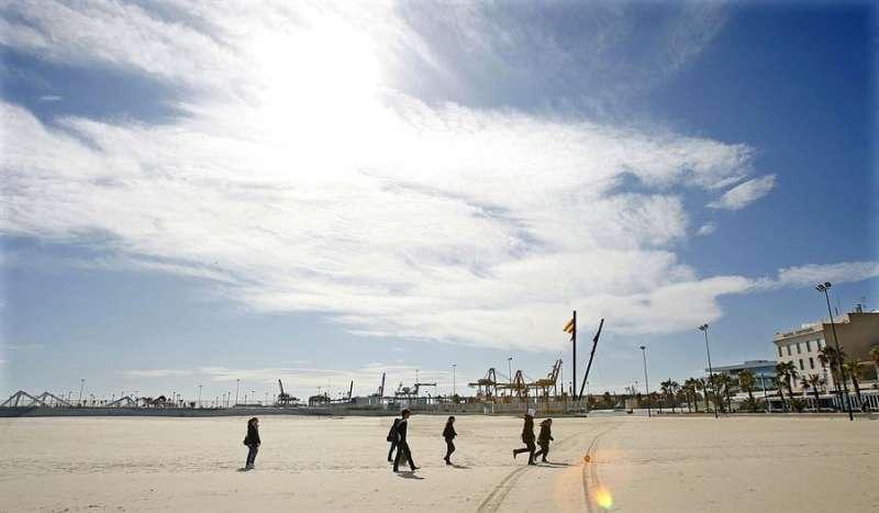 Varios jóvenes pasean este mediodía por la playa de Las Arenas de Valencia en un día poco nuboso. EFE/Archivo