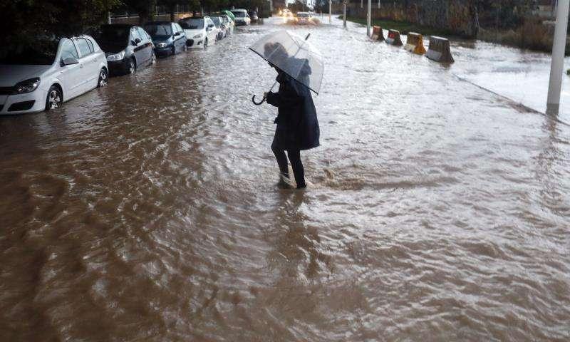 Una persona cruza una calle inundada durante una de los �ltimos temporales que azotaron la Comunitat. EFE/Archivo