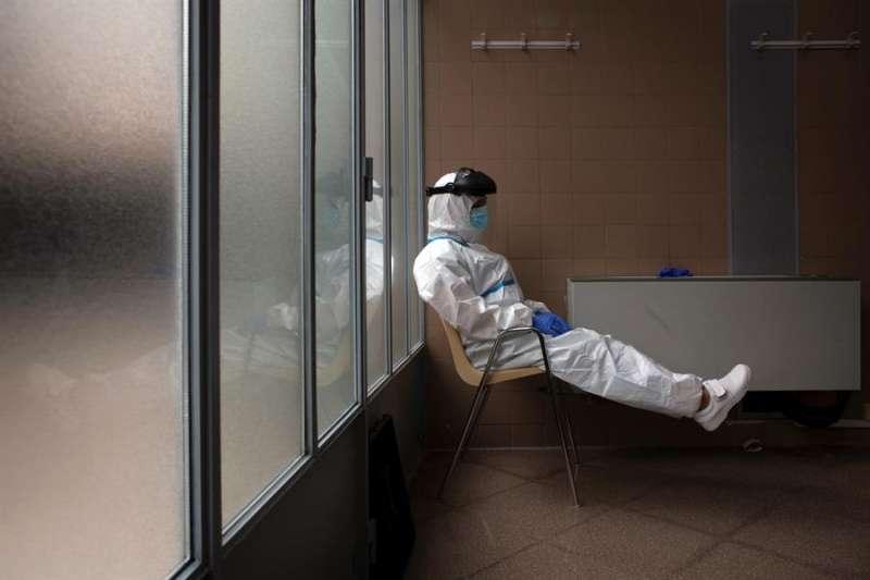 Una profesional sanitaria descansa tras varias horas realizando pruebas PCR. EFE/Enric Fontcuberta/Archivo