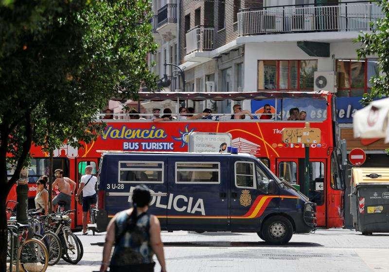Un autobús turístico pasa ante un furgón de la Policía Nacional estacionado en una calle peatonal del centro de Valencia. EFE/Archivo