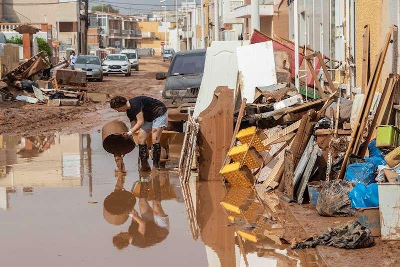 Una mujer vierte lodo en la calle en la localidad de Los Nietos, en Cartagena. EFE
