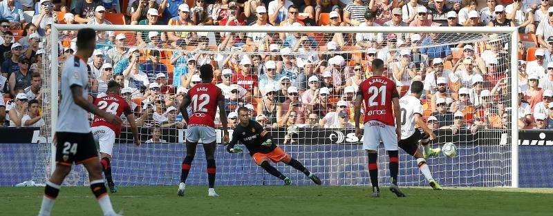 El centrocampista español del Valencia CF Dani Parejo (d) lanza uno de los penaltis durante el partido ante el RCD Mallorca. EFE