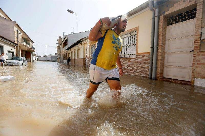 Un vecino de la población alicantina de Las Heredades con sacos de arena para colocarlos este domingo en la puerta de sus casas tras las inundaciones que ha provocado la gota fría. EFE/Manuel Lorenzo