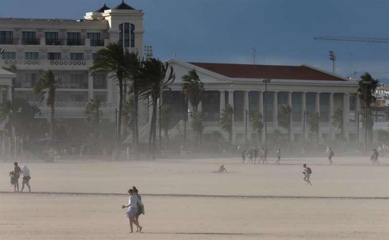 Varias personas abandonan la playa de la Malvarrosa bajo un intenso viento. EFE/Juan Carlos Cárdenas