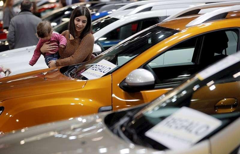 Una mujer contempla un vehículo en la Feria del Automóvil de València. EFE/Kai Försterling