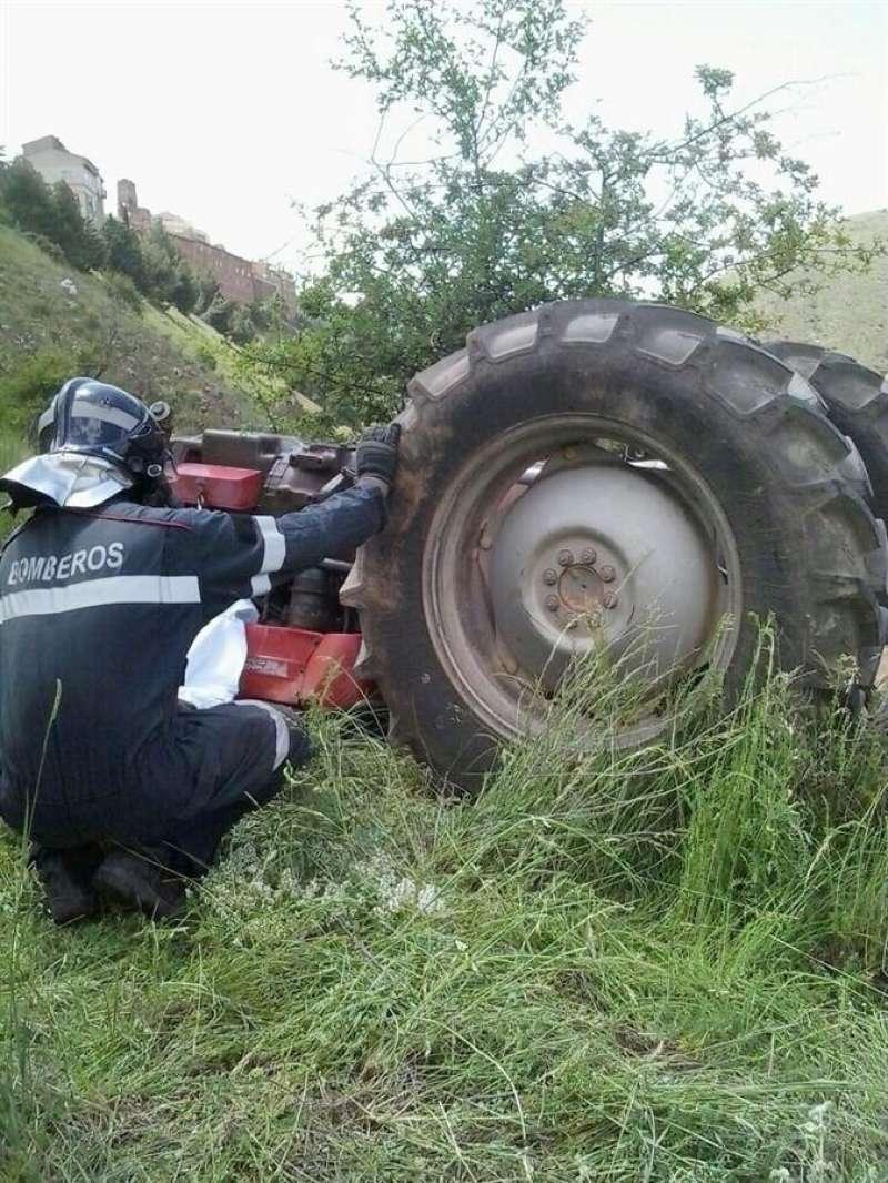 Un bombero inspecciona un tractor accidentado, en una imagen de archivo. EFE/Archivo