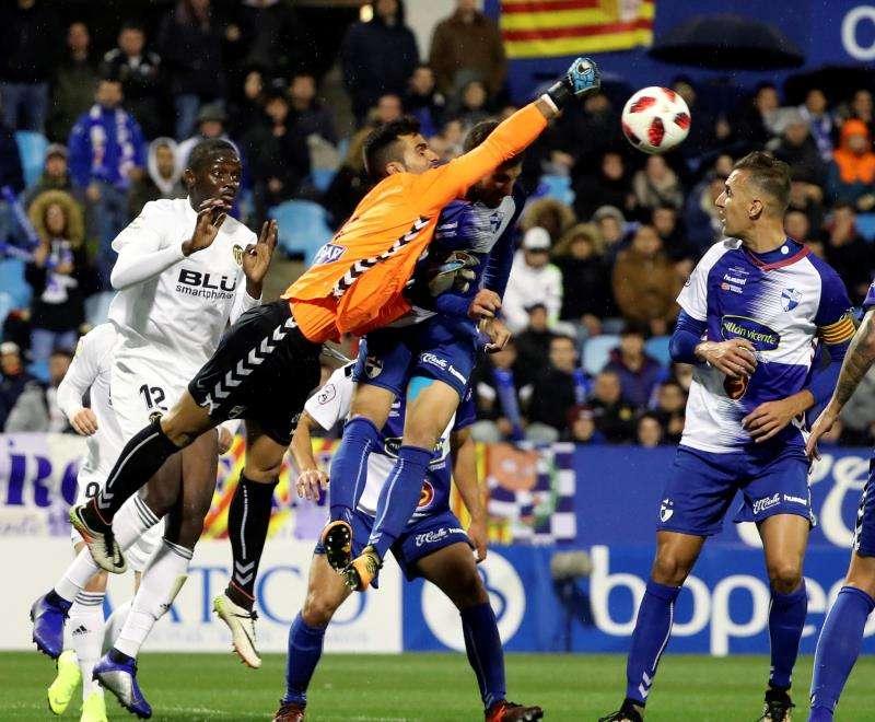 El portero del CD Ebro Salva (c) despeja ante el defensa francés del Valencia Mouctar Diakhaby (i), en partido de ida de dieciseisavos de final de la Copa del Rey que se ha disputado en el estadio de La Romareda. EFE