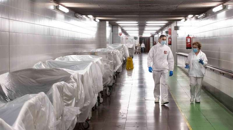 Dos sanitarios en el pasillo de un hospital con decenas de camas preparadas en previsión por la pandemia del Covid 19. EFE/Marcial Guillén