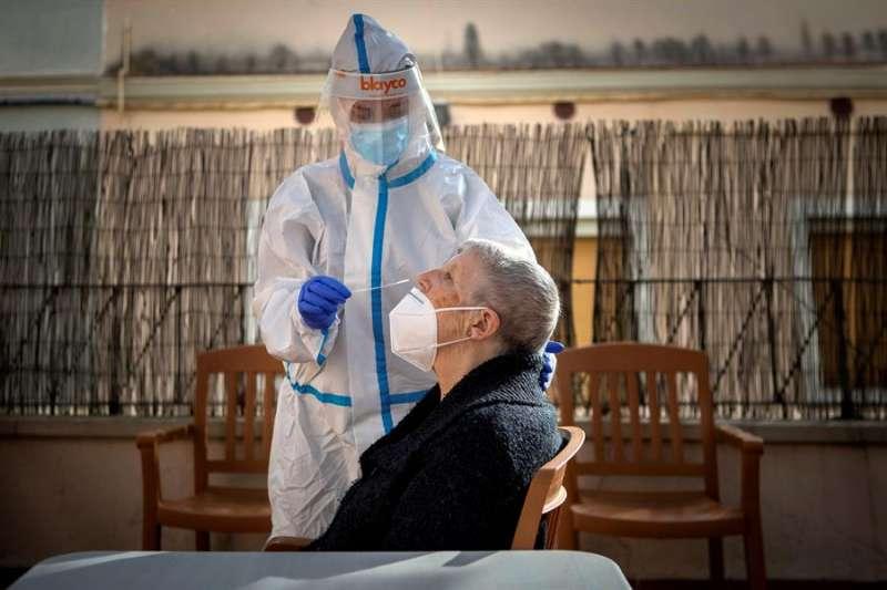 Una profesional sanitaria realiza un test PCR a una residente de una residencia. EFE