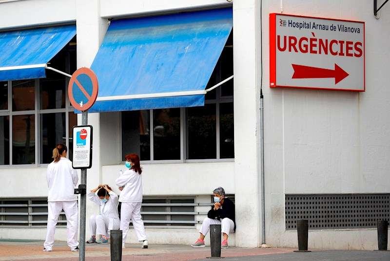Personal sanitario del Hospital Arnau de Vilanova descansa unos minutos ante la puerta de urgencias, hoy durante el sexto día del estado de alarma decretado por el Gobierno. EFE