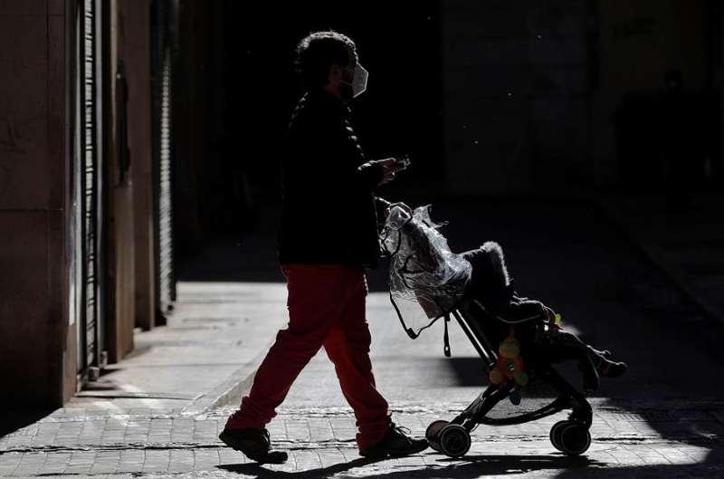 Un hombre pasea con un carrito de bebé por la ciudad de Valencia. EFE
