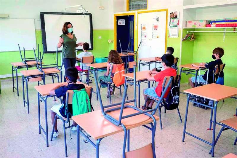 Una maestra imparte clase en un colegio con niños guardando la distancia de seguridad.  / EFE