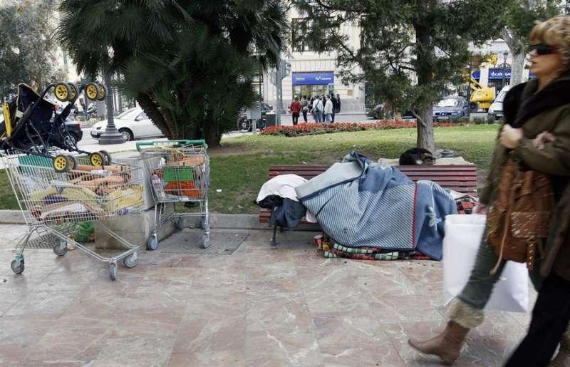 Un persona sin hogar en un banco de la ciudad de València. EFE/Juan Carlos Cárdenas/Archivo