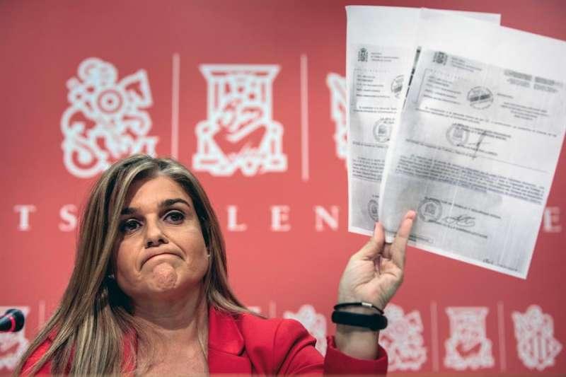 La síndica adjunta del PP en Les Corts, Eva Ortiz, muestra documentación sobre estas ayudas en una rueda de prensa. EFE