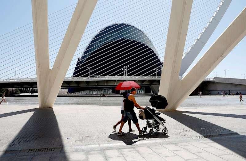 Una pareja se protege del sol ante el Ágora de la Ciudad de las Ciencias, en València.