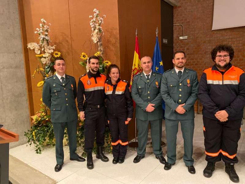 Los tres guardias civiles condecorados, junto a miembros de Protección Civil. EPDA