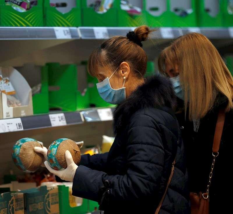 Dos mujeres con mascarilla y guantes se abastecen en un supermercado. EFE