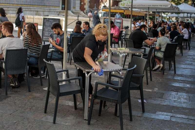 Una camarera desinfecta una mesa de una terraza en el centro de Valencia. EFE/Archivo