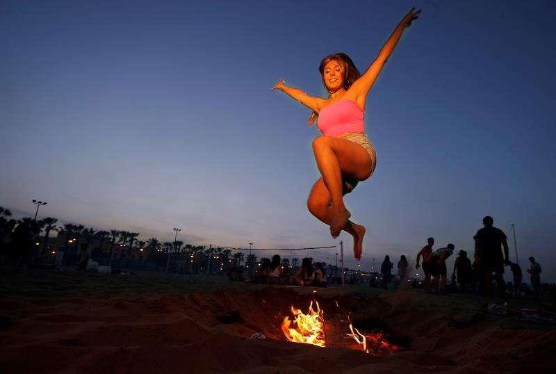 Una joven salta la hoguera que ha encendido junto a un grupo de amigos para celebrar la Noche de San Juan. EFE