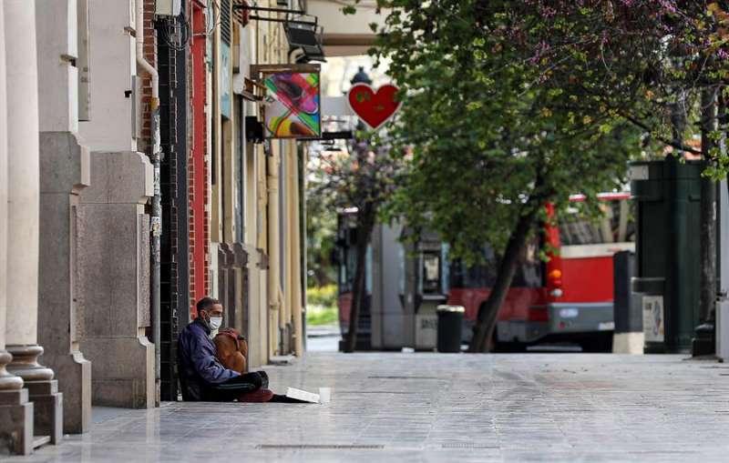 Un hombre, protegido con una mascarilla, pide una ayuda, en la plaza del Ayuntamiento de Valencia. EFE