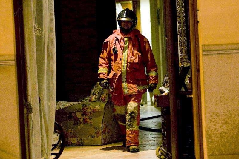 Un bombero sale de la vivienda incendiada. EFE/Archivo