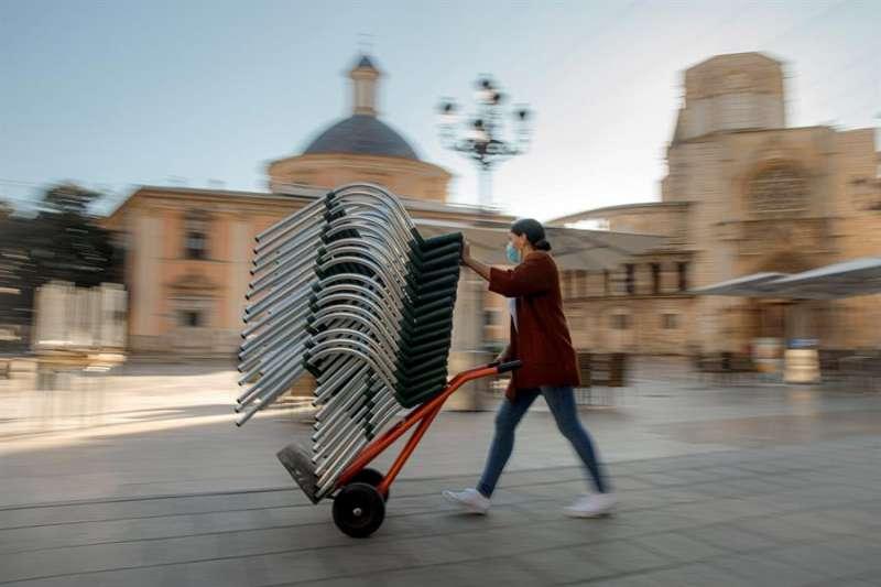 Una persona monta la terraza de un bar de una céntrica plaza de València. EFE.