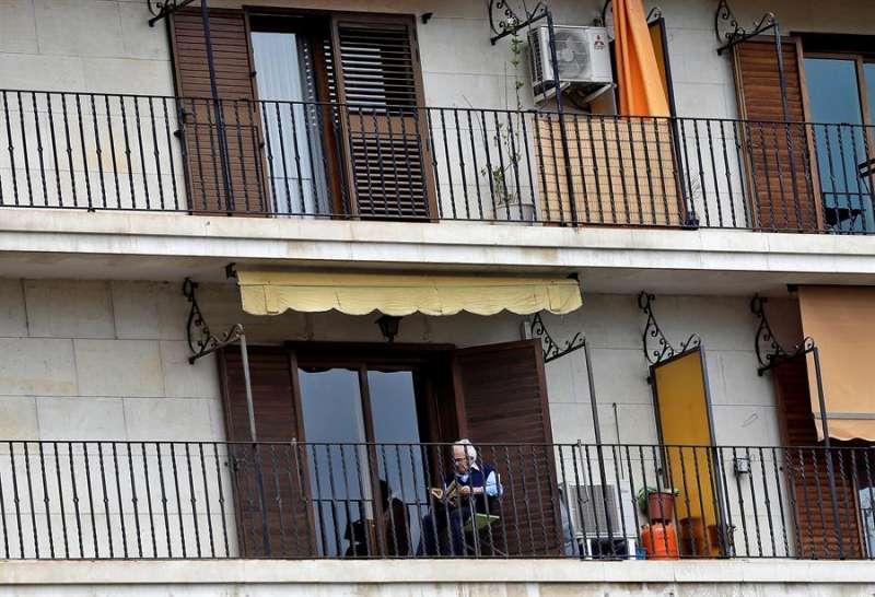 Un hombre lee en el balcón de su vivienda en una imagen de archivo. EFE