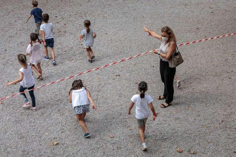 Varios niños y niñas del colegio se dirigen a la zona acotada para el recreo, durante un día de clase, en una imagen de estos días. EFE/Biel Aliño