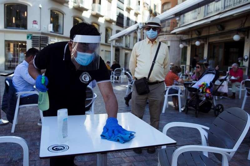 Un camarero desinfectando una mesa. EFE