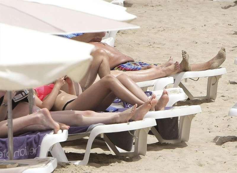 Varias personas toman el sol este mediodía en la playa del Postiguet de Alicante. EFE
