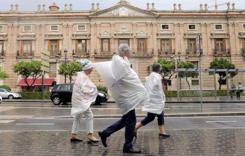 Tres personas se protegen con bolsas de plástico un día de lluvia. EFE/Archivo