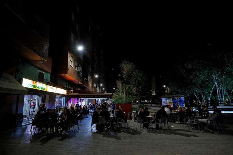 Decenas de jóvenes apuran sus bebidas y los últimos minutos, en una conocida zona de ocio de Valencia, antes de la entrada en vigor del toque de queda, en una imagen de octubre de 2020. EFE/Manuel Bruque.