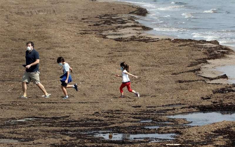 En la imagen, un padre con sus dos hijos, en la Playa de la Malvarrosa de Valencia. EFE/Archivo