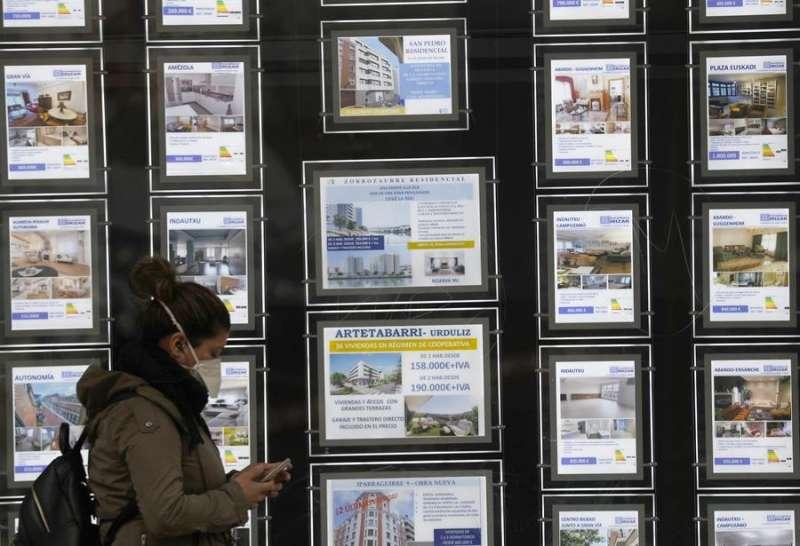 Una mujer pasa por delante de un portal inmobiliario de venta y alquiler. EFE
