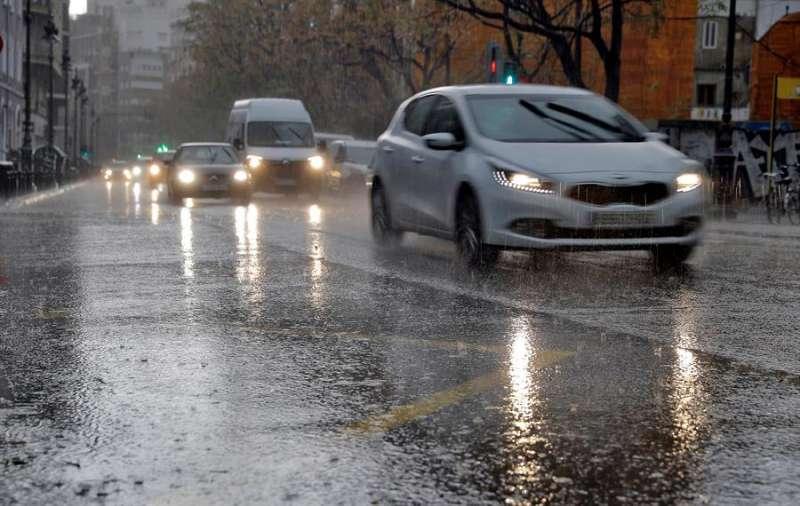 Varios vehículos circulan bajo una intensa lluvia en la ciudad de València. EFE