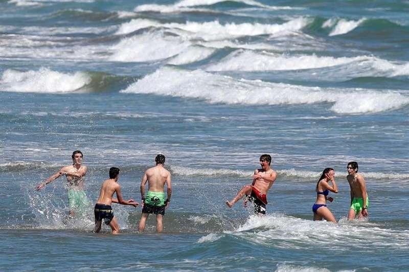 Un grupo de jóvenes disfruta de un baño en aguas de la playa de la Malvarrosa EFE/Kai Försterling