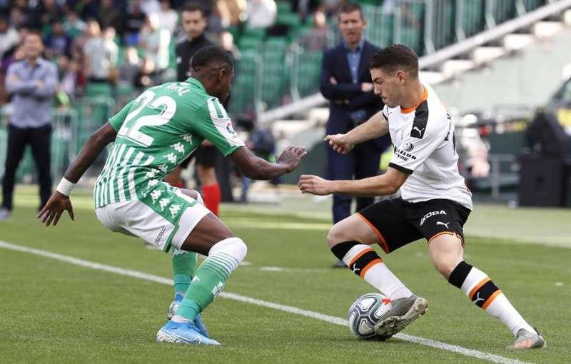 El delantero del Valencia Manuel Vallejo (d) disputa el balón con el defensor brasileño del Real Betis Emerson (i). EFE/Archivo