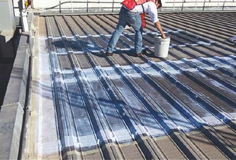 Unos operarios trabajan con la pintura aislante capaz de reducir hasta un 15% la temperatura del interior de los edificios, en una imagen de la UPV.
