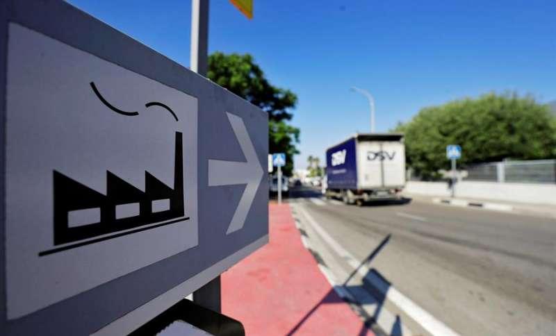 Un camión pasa junto a una señal que indica el camino a un polígono industrial.