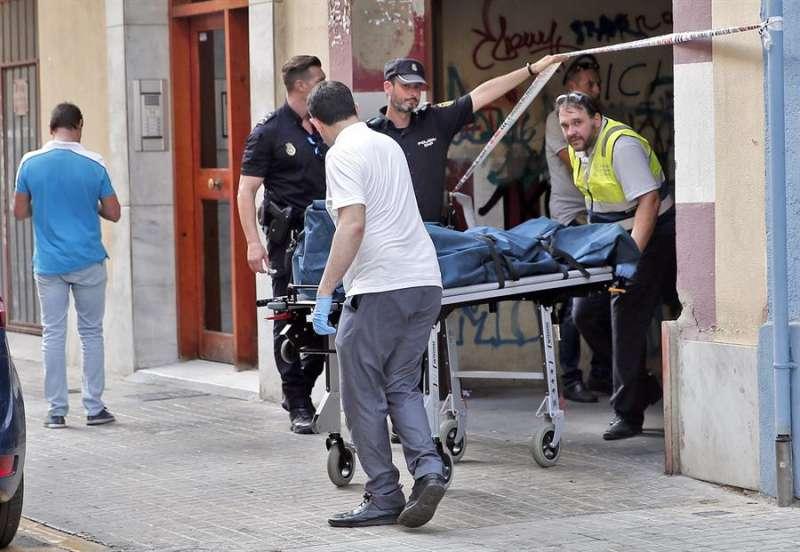 Dos miembros del retén fúnebre retiran el cadáver de la víctima de este crimen, en una imagen de agosto de 2017. EFE/Manuel Bruque/Archivo