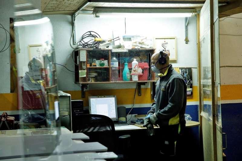 Un trabajador de una empresa de rotulación de Manises (Valencia) prepara mamparas de metacrilato. EFE