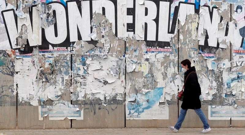 Imagen de archivo de una persona con mascarilla pasando bajo un letrero de Wonderland en Valencia durante la fase de descenso de la tercera ola de la pandemia. EFE/Kai Försterling.