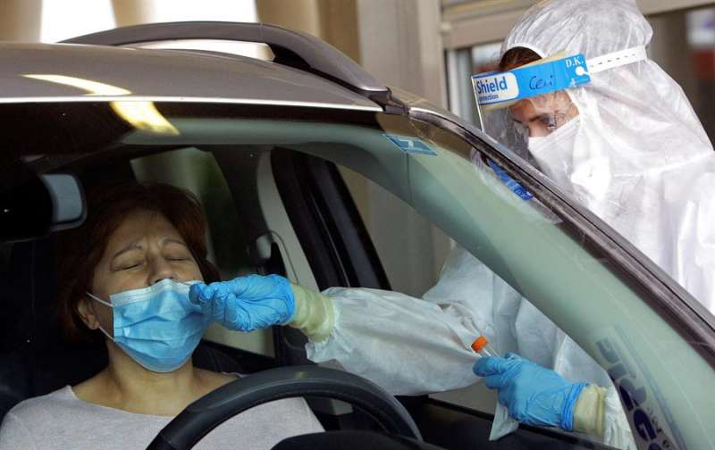 Una sanitaria protegida con EPI toma una muestra para una prueba PCR en un hospital valenciano. EFE