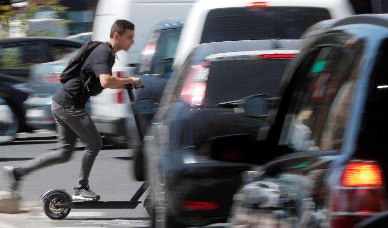 Un joven en patinete circula entre varios coches. EFE/Archivo