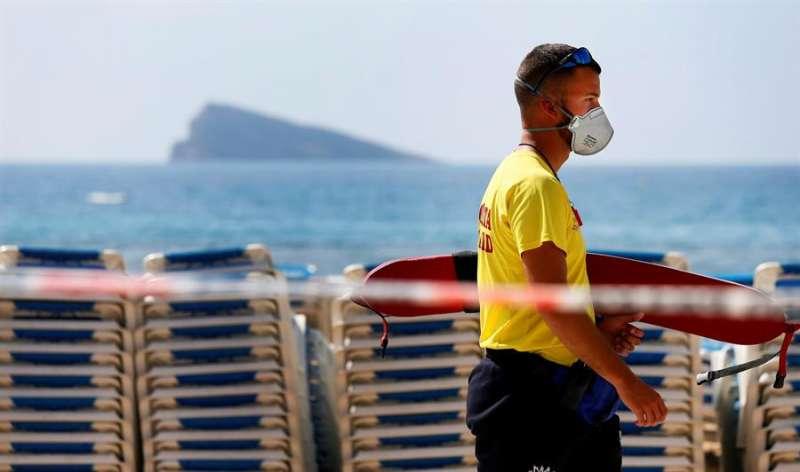 Un joven con mascarilla en una zona de costa. EFE
