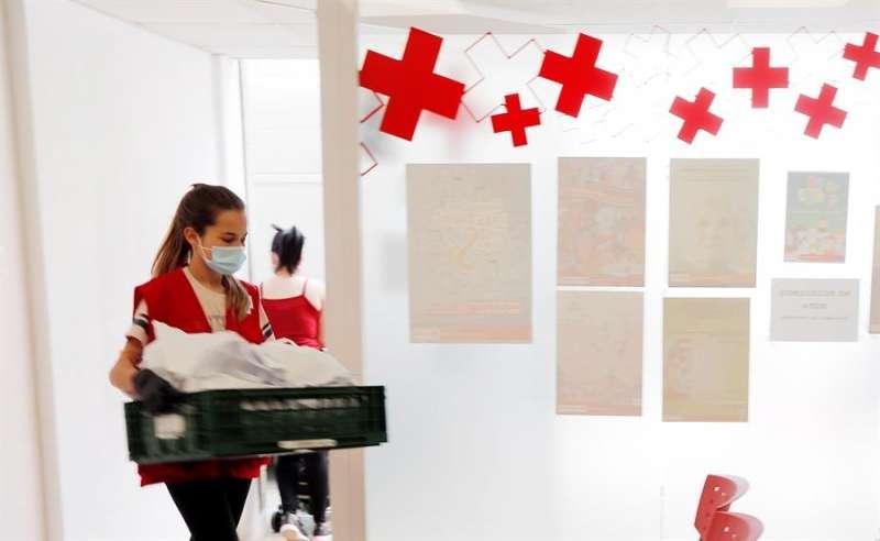 Una voluntaria de Cruz Roja lleva bolsas de alimentos un reparto de comida. EFE