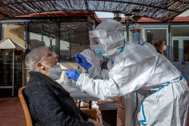 Dos profesionales sanitarias realizan un test PCR a una residente de una residencia. EFE/Archivo